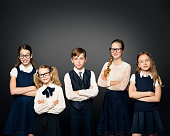 School Children Group, Girls and Boy Students In Uniform over Black Background