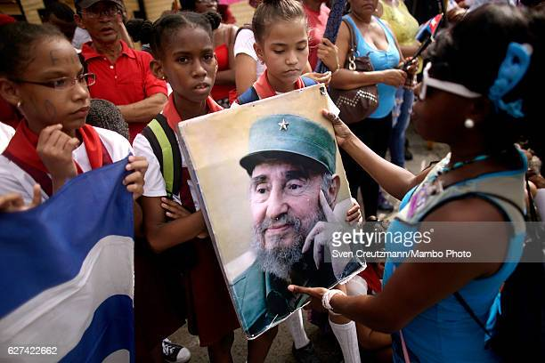 School children hold a photograph of former Cuban President Fidel Castro as they wait for his remains pass by on their fourday journey across the...