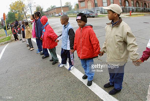 School children hold hands along a Chicago street October 22 2001 as part of National Red Ribbon Week activities Community residents students...