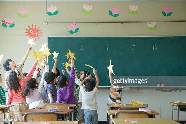 School children (4-11) holding stars in classroom