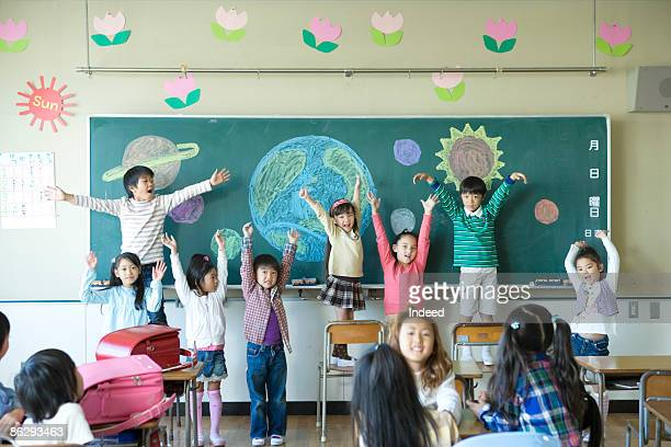 School children in classroom, raising arms