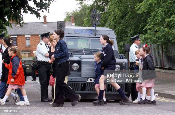 School children in the Ardoyne area of North Belfast walk past police when they are forced to take an alternative route to school away from a...
