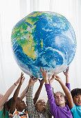 School children (8-9) lifting inflatable globe