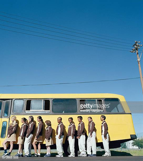 School children (9-16) lined up at side of school bus