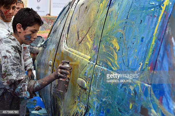 School children paint a car wreck during a performance by Bulgarian artist Alexander Jakhnagiev called 'Crash Art' on October 17 2014 in Rome 'Crash...