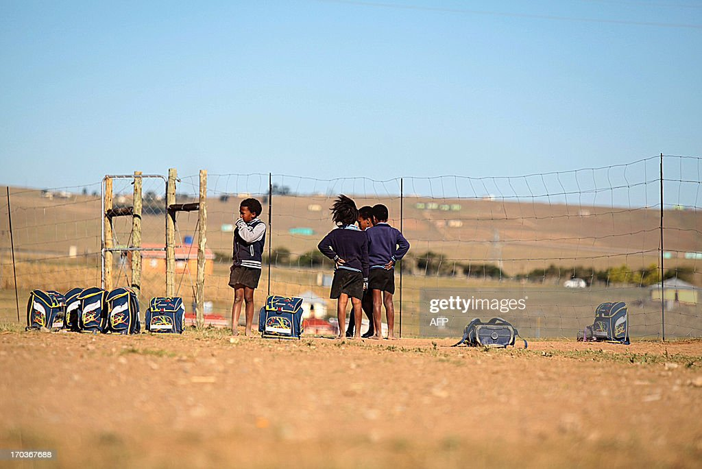 School children play on June 11, 2013 on a dusty playground at the Nelson Mandela No-Moscow Primary School in Qunu, near Mthatha in the Eastern Cape, where former South African president Nelson Mandela grew up before returning to the village after his term as president. . In the rural South African village where he once roamed as a boy, the lowered flags at Nelson Mandela's homestead are a constant reminder of his absence. Ill health forced the 94-year-old, now battling a lung infection in hospital, to leave Qunu months ago, but his latest illness has sparked prayers, worry and resignation in his home town.