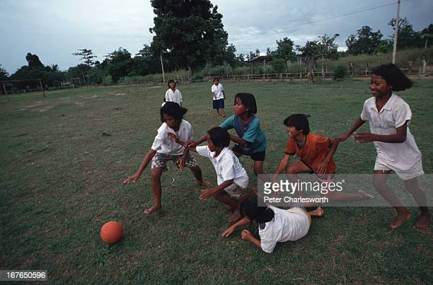 School children play with a ball in a field near a Government school in rural Thailand near Surin Many of these kids come from impoverished families...
