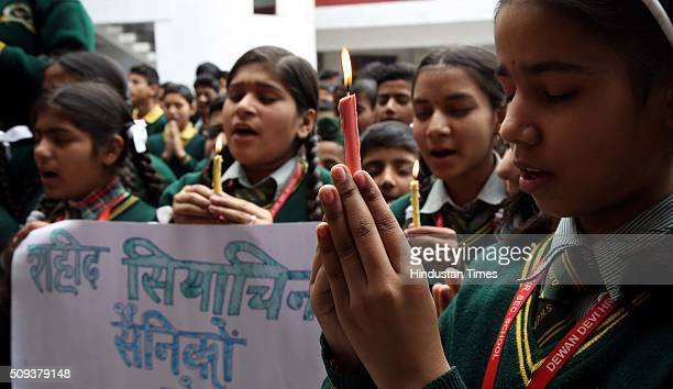 School children pray and hold placards for Siachen Glacier survivor Indian soldier Lance Naik Hanumanthappa Koppad on February 10 2016 in Jammu India...