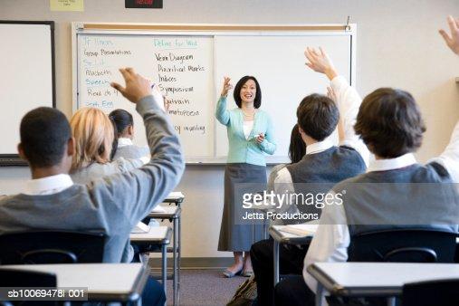 School children (14-18) raising hands in class : Stock Photo