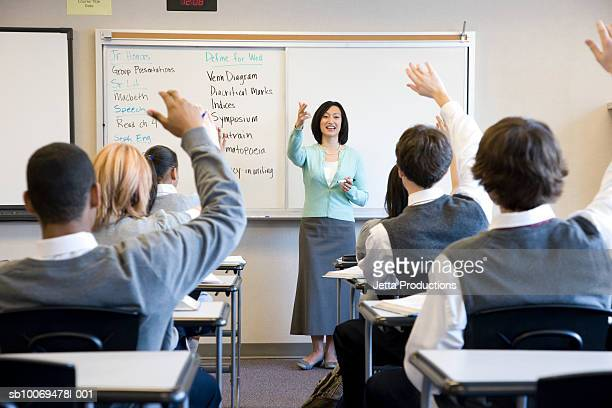 School children (14-18) raising hands in class