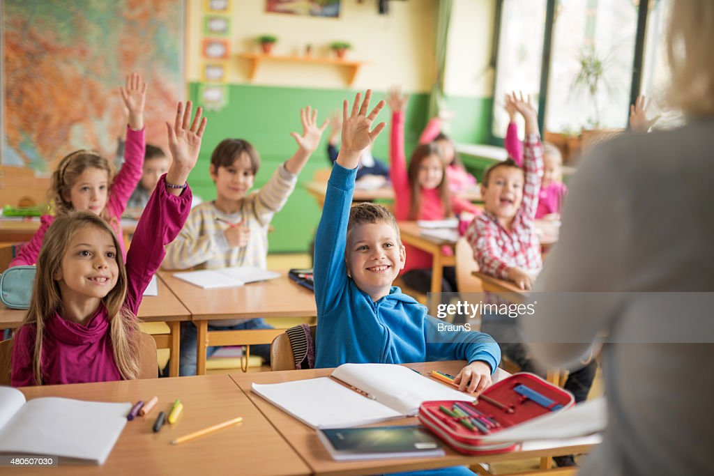 School children raising their hands ready to answer the question. : Stock Photo