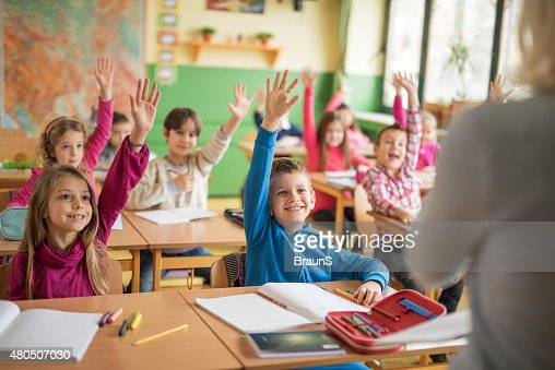 School children raising their hands ready to answer the question.