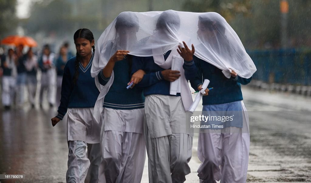 School children return after taking exam as it rains with overcast sky near Mayur Vihar, on February 16, 2013 in New Delhi, India. The National capital witnessed a total of 18.6 mm of rains since yesterday and the weather is likely to remain cloudy for another day.