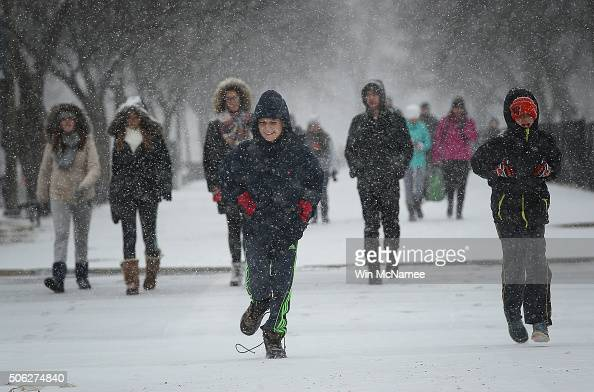 School children run along the National Mall as snow begins to fall January 22 2016 in Washington DC A major snowstorm is forecasted for the East...