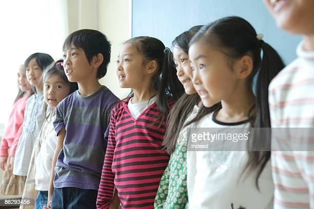 School children (6-9) singing in classroom