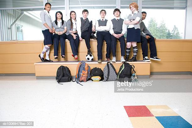 School children (14-19) sitting in school corridor, portrait