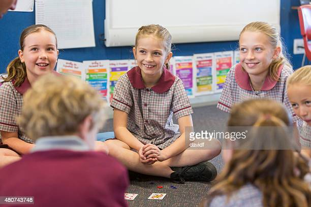 School Children Sitting Playing A Maths Game With Cards