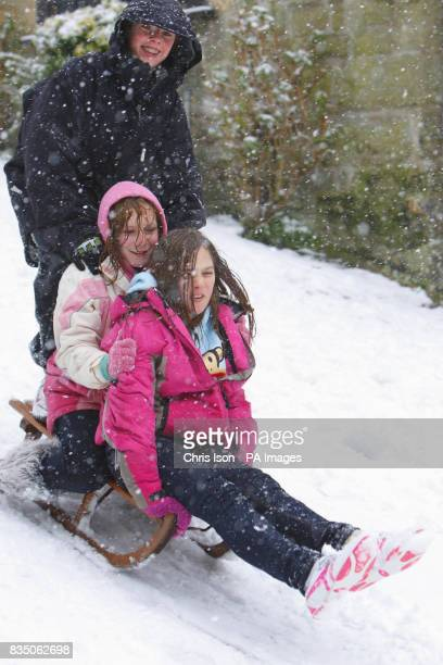 School children sledge down the iconic Gold Hill in Shaftesbury Dorset where it has snowed everyday this week