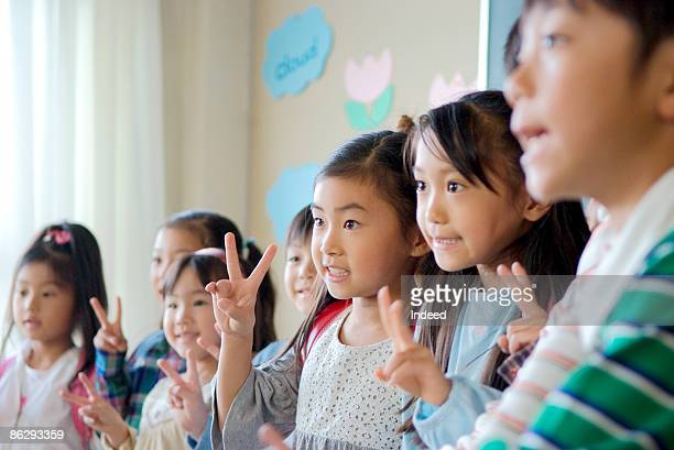 School children (6-11) smiling, making peace sign