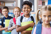 Portrait of a happy multiethnic children holding books and wearing backpack at primary school. Schoolboys and cute girls in a row holding notebook and looking at camera. Portrait of a elementary child