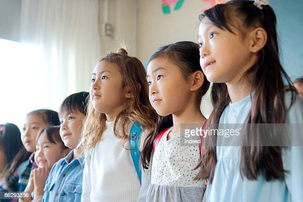 School children (6-9) standing, looking away