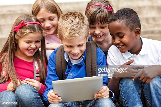 School children using digital tablet outside