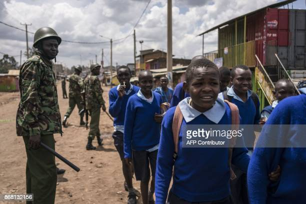 TOPSHOT School children walk for shelter during a standoff between Kenyan police and supporters of Kenyan opposition leader in Kawangware outside...