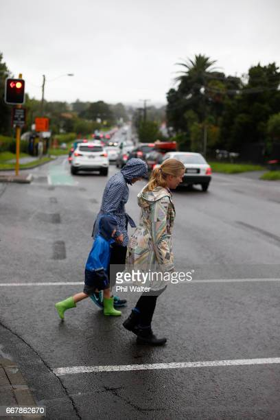 School children walk home from school after some schools shut early before the worst of Cyclone Cook is due to reach landfall on April 14 2017 in...