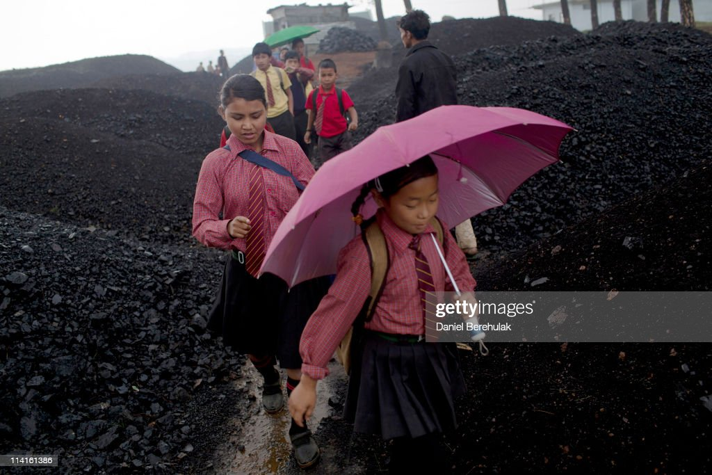 School children walk through a coal depot on their way home from school on April 14, 2011 in Lad Rymbai, in the district of Jaintia Hills, India. Local schools in the area, providing free tuition, find it difficult to convince parents of the benefits of education, as children are seen as sources of income. The lure of the mines is stronger than that of the classroom. The Jaintia hills, located in India's far North East state of Meghalaya, miners descend to great depths on slippery, rickety wooden ladders. Children and adults squeeze into rat hole like tunnels in thousands of privately owned and unregulated mines, extracting coal with their hands or primitive tools and no safety equipment. Workers can earn as much as 150 USD per week or 30,000 Rupees per month, significantly higher than the national average of 15 USD per day. After traversing treacherous mountain roads, the coal is delivered to neighbouring Bangladesh and to Assam from where it is distributed all over India, to be used primarily for power generation and as a source of fuel in cement plants. Many workers leave homes in neighbouring states, and countries, like Bangladesh and Nepal, hoping to escape poverty and improve their quality of life. Some send money back to loved ones at home, whilst many others squander their earnings on alcohol, drugs and prostitution in the dusty, coal mining towns like Lad Rymbai. Some of the labor is forced, and an Indian NGO group, Impulse, estimates that 5,000 privately-owned coal mines in Jaintia Hills employed some 70,000 child miners. The government of Meghalaya refuted this figure, claiming that the mines had only 222 minor workers. Despite the ever present dangers and hardships, children, migrants and locals flock to the mines hoping to strike it rich in India's wild east.