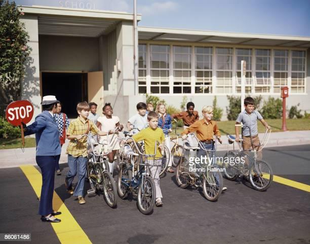 School children walking on crosswalk with bicycles