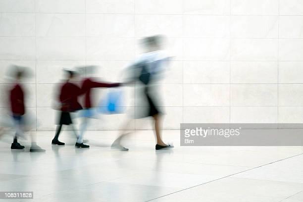 School children walking with female teacher, motion blur