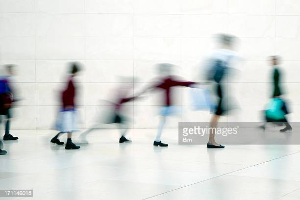 School children walking with teacher, motion blur
