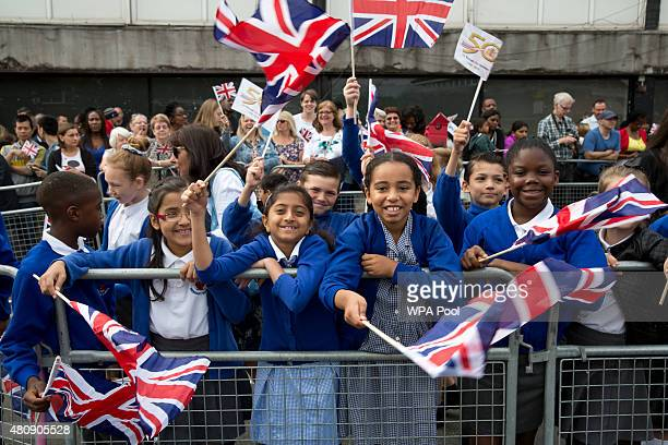 School children wave flags during Queen Elizabeth II and Prince Philip Duke of Edinburgh's visit to Chadwell Heath Community Centre on July 16 in...