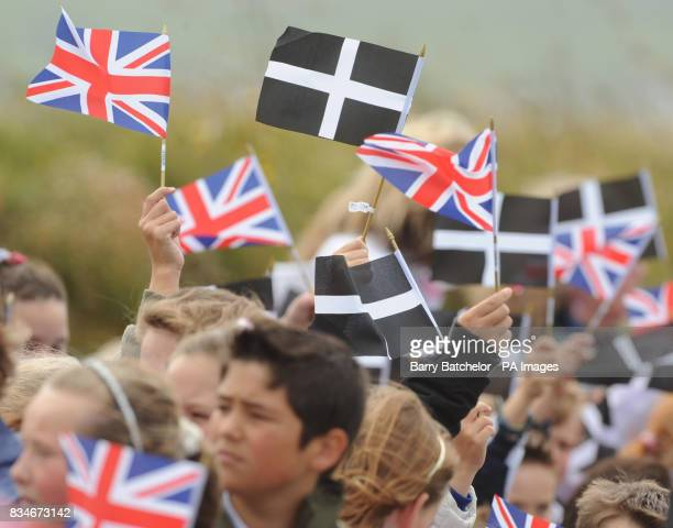 School children wave Union flags and Cornish flags alongside each other as they greet the arrival of the Prince of Wales and the Duchess of Cornwall...