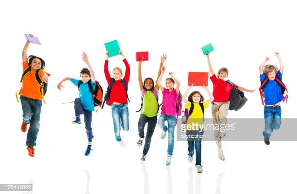 School children with backpacks and books jumping.