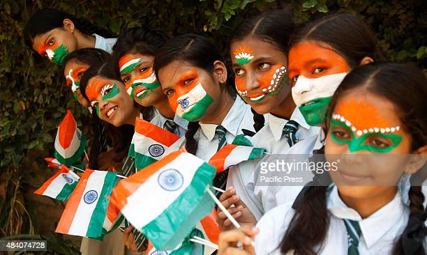 School children with the Indian flag painted on their faces celebrate Independence Day