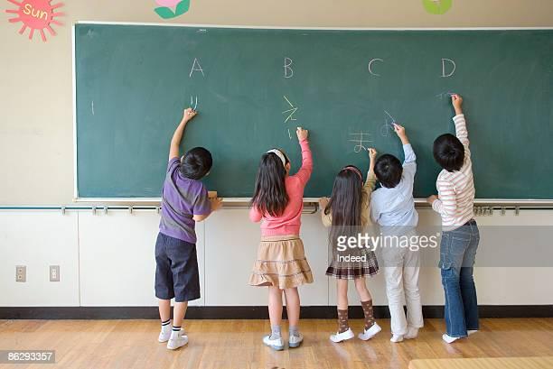 School children (6-9) writing on blackbaord