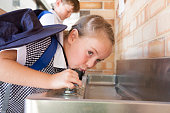 A school child drinking from a drinking fountain, Australia
