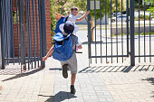 Two school children running out the school gate at the end of the day.