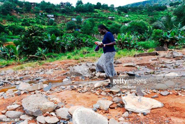 School director AnnMarie Caulker walks in Freetown on August 18 2017 A week after Sierra Leone's capital Freetown was struck by flooding and...