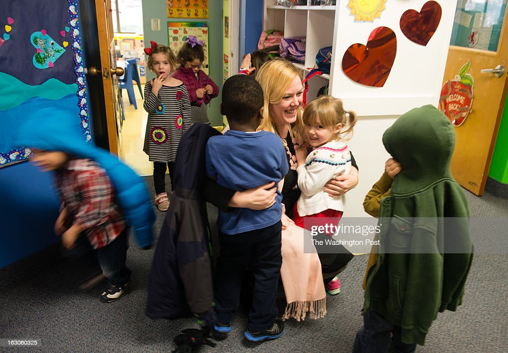 School employee, Jennifer Robertson, center, gives a hug to her daughter, Julia Robertson, 4, right, and AJ Valbrune, 3. At the St. Andrews Episcopal School in Potomac, MD, they use brain research to inform teaching and learning. The school has the only K-12 school center for teaching based on brain research in the country.