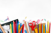 """""""Back to School"""" concept with school supplies on white background. They are on the bottom border of it, middle of the chalkboard is empty, so you may write, or add something on it."""