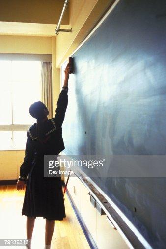 School girl cleaning the blackboard : Stock Photo