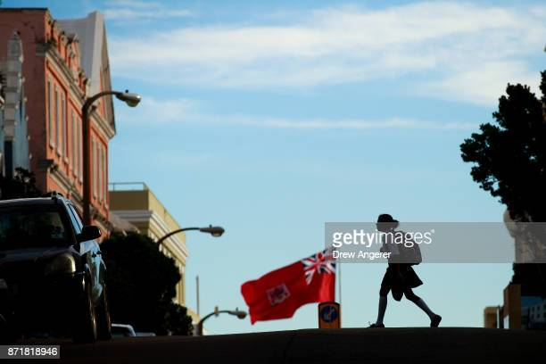 A school girl crosses the street as the flag of Bermuda flies in the city of Hamilton Bermuda November 8 2017 In series of leaks made public by the...