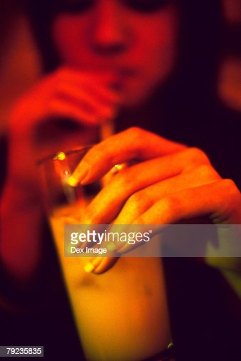 School girl drinking a glass of juice with a straw : Stock Photo