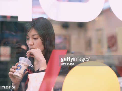 School girl drinking in a caf? : Stock Photo