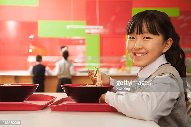 School girl eats noodles in school cafeteria