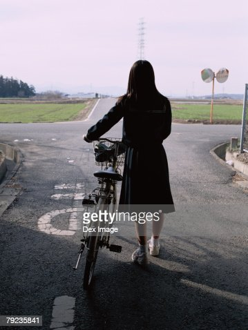 School girl holding a bicycle : Stock Photo
