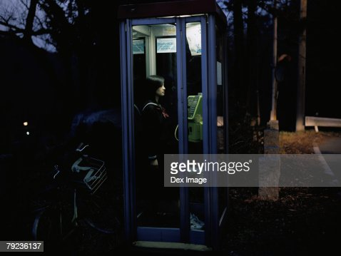School girl in a public telephone booth : Stock Photo