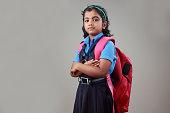 Portrait of a school girl wearing uniform and bag